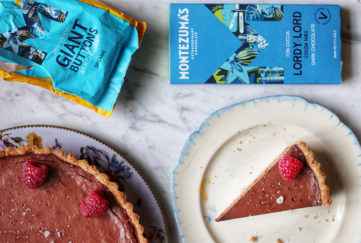 Chocolate tart decorated with raspberries, bag of giant chocolate buttons and a bar of Montezuma's Lordy Lord coca nibs dark chocolate