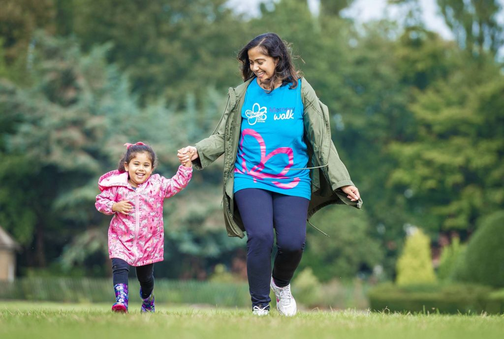Mum, wearing Memory Walk T-shirt, and 5 year old daughter laughing as they walk in the park