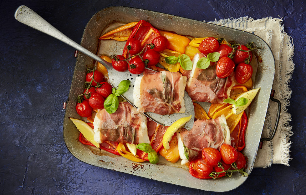Brightly coloured tomatoes, fresh basil, pieces of fish wrapped in parma ham and other vegetables in a baking tray