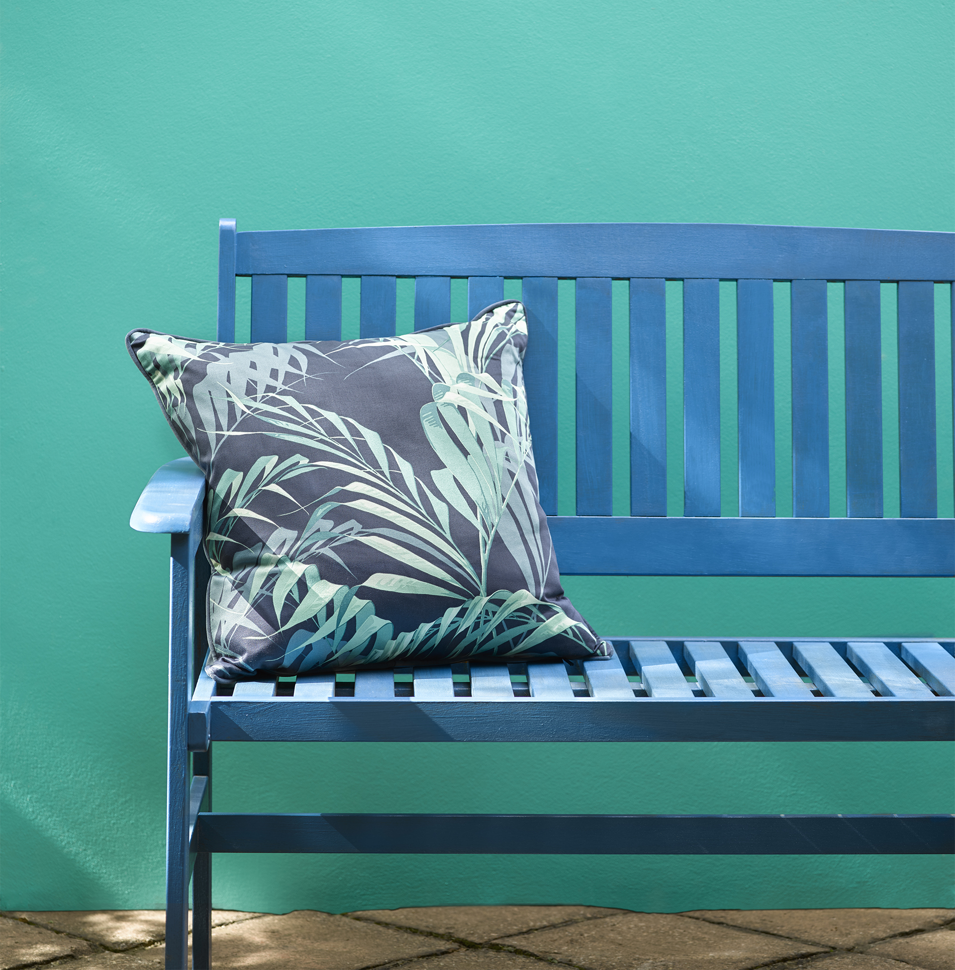 Royal blue painted bench with blue/green fern patterned cushion against bright turquoise wall, tiled floor