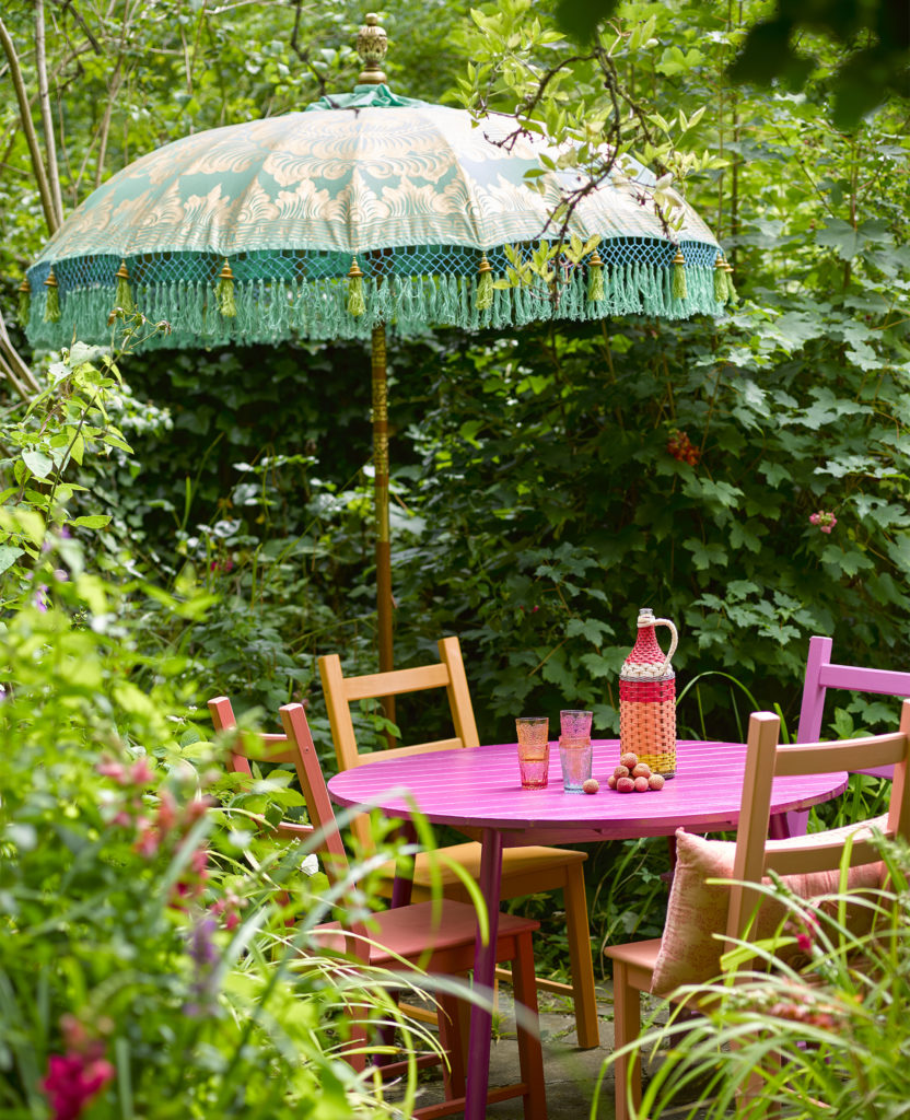 Outdoor table and chairs painted pink and orange with green umbrella and climbing plants all around