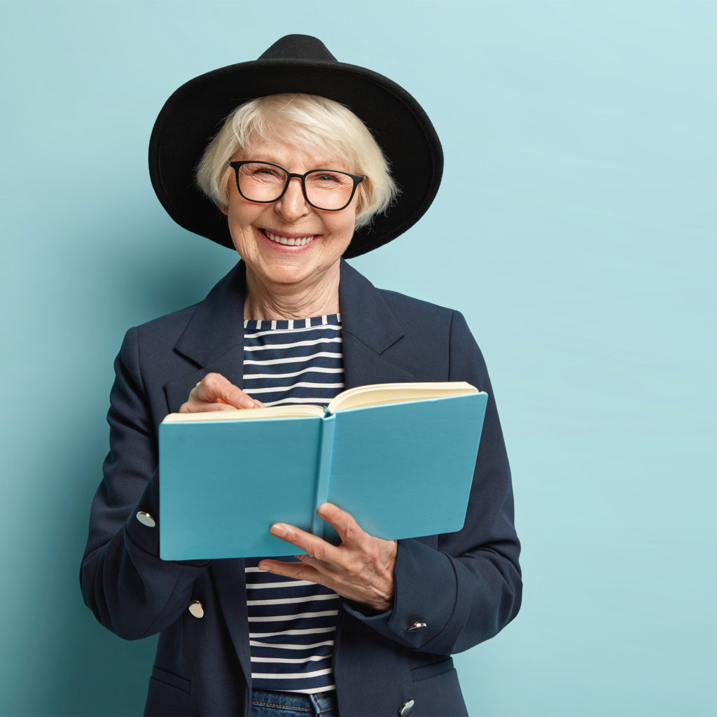 Mature lady smiling as she writes in a blue notebook