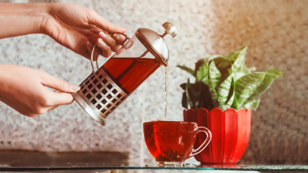 Woman's hands pouring red tea out of cafetiere