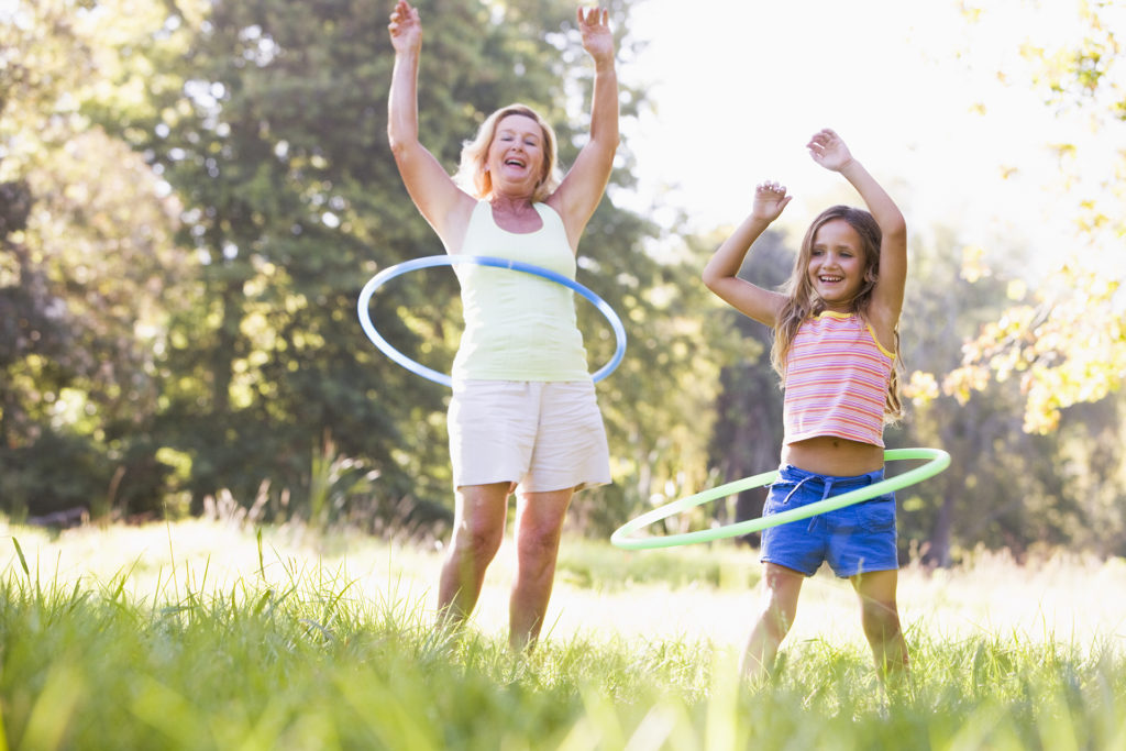 Grandmother and granddaughter at a park hula hooping and smiling;