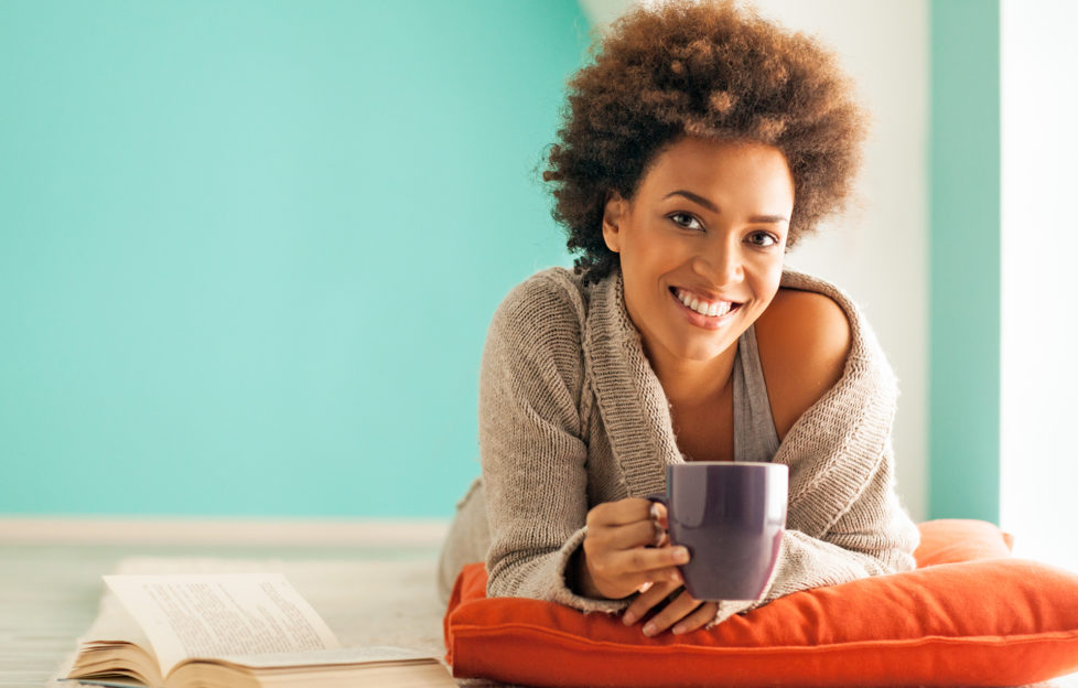 Beautiful young African woman enjoying a cup of coffee while relaxing at home.;