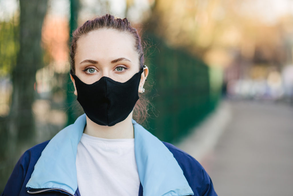Closeup pretty woman wearing a face mask to protect against pollution or disease.COVID-19 Pandemic Coronavirus Young girl in city street wearing face protective mask.