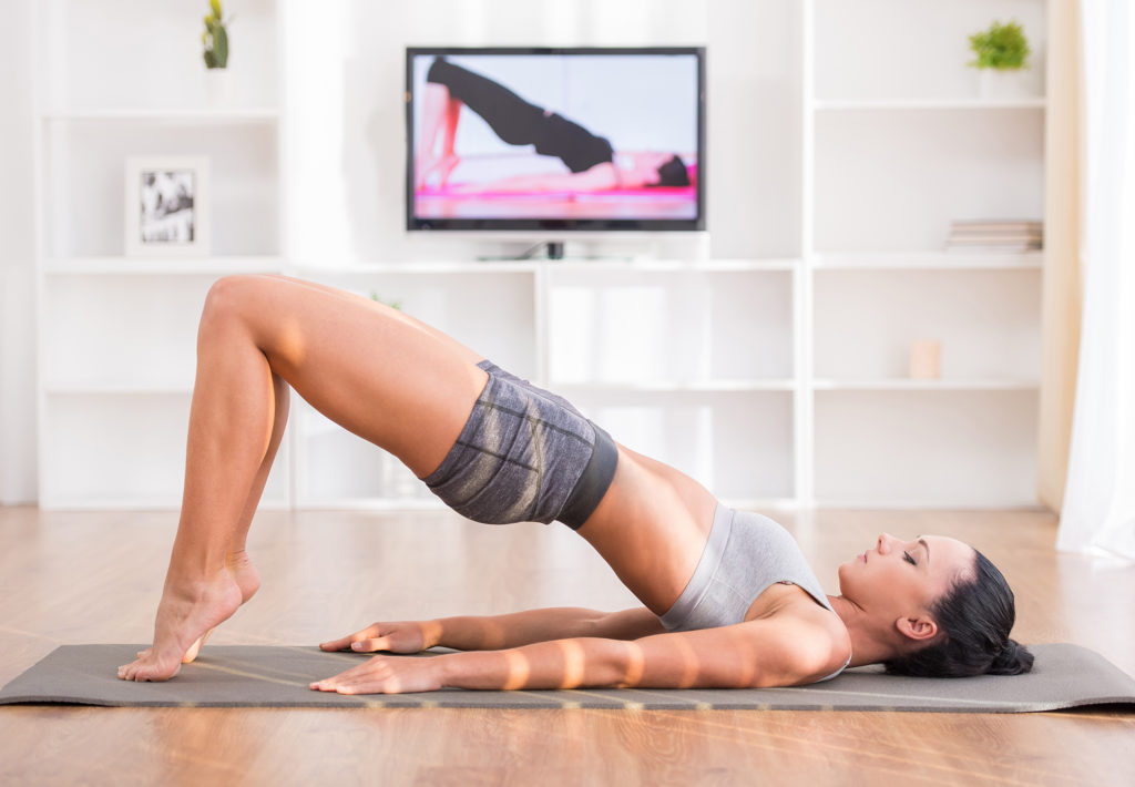 Woman is doing fitness at home on her living room floor while watching and participating in a class.;