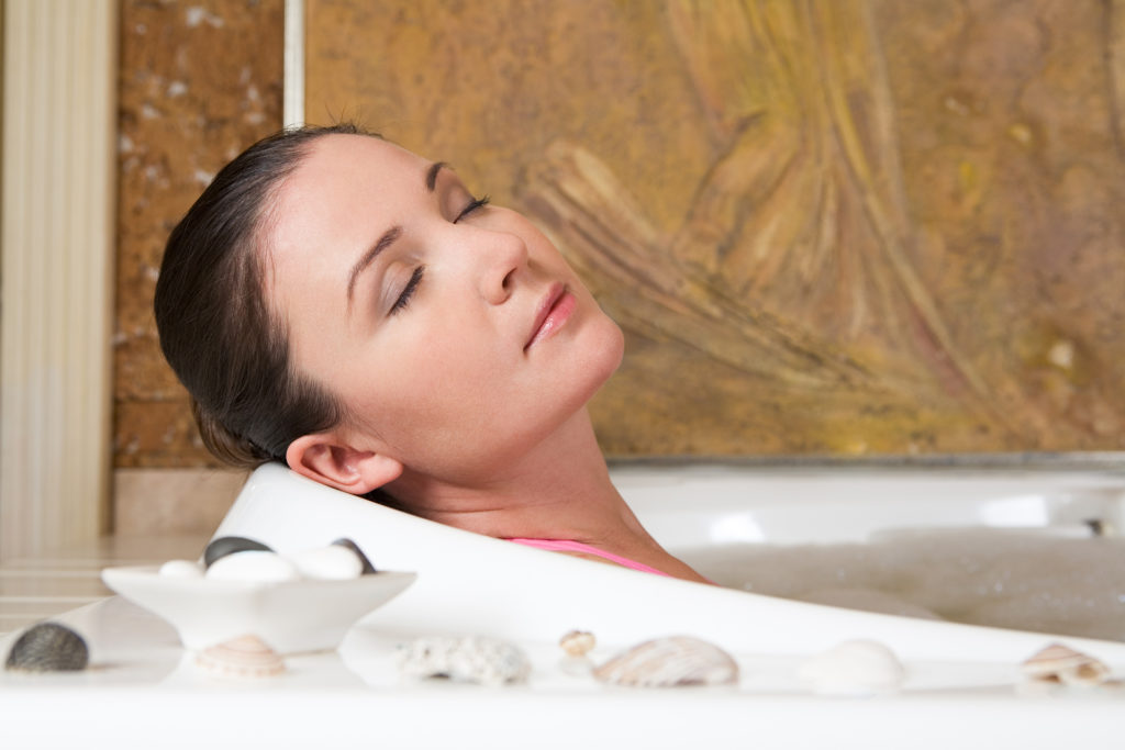 Image of relaxing woman with closed eyes having pleasant bath with seashells near by;