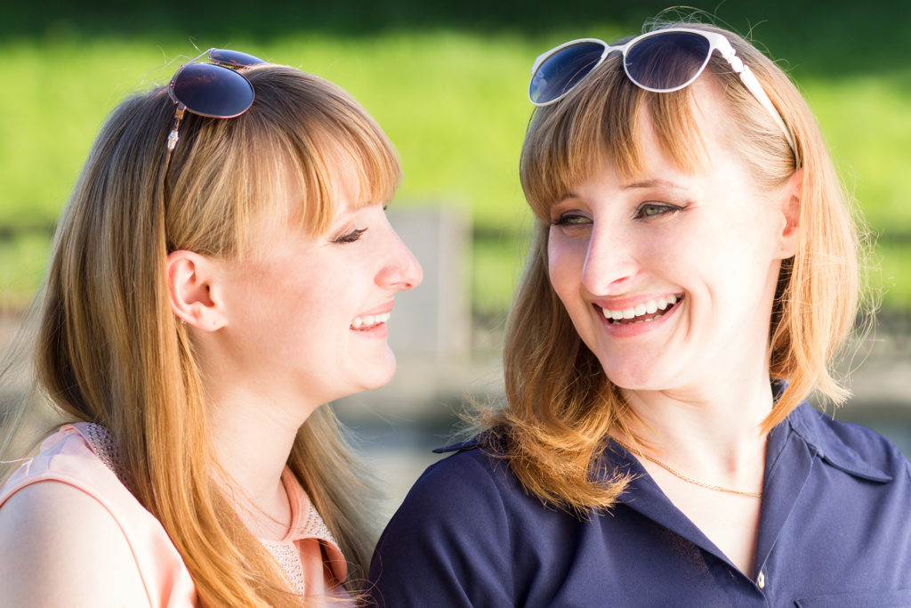 Pretty twins girls having fun at outdoor summer park. Young student sisters laughing talking each other;