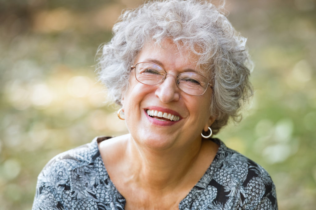 Portrait of senior woman smiling and looking at camera. Cheerful mature woman wearing eyeglasses in the park. Happy old woman with grey hair smiling. Carefree and positive retired woman.;