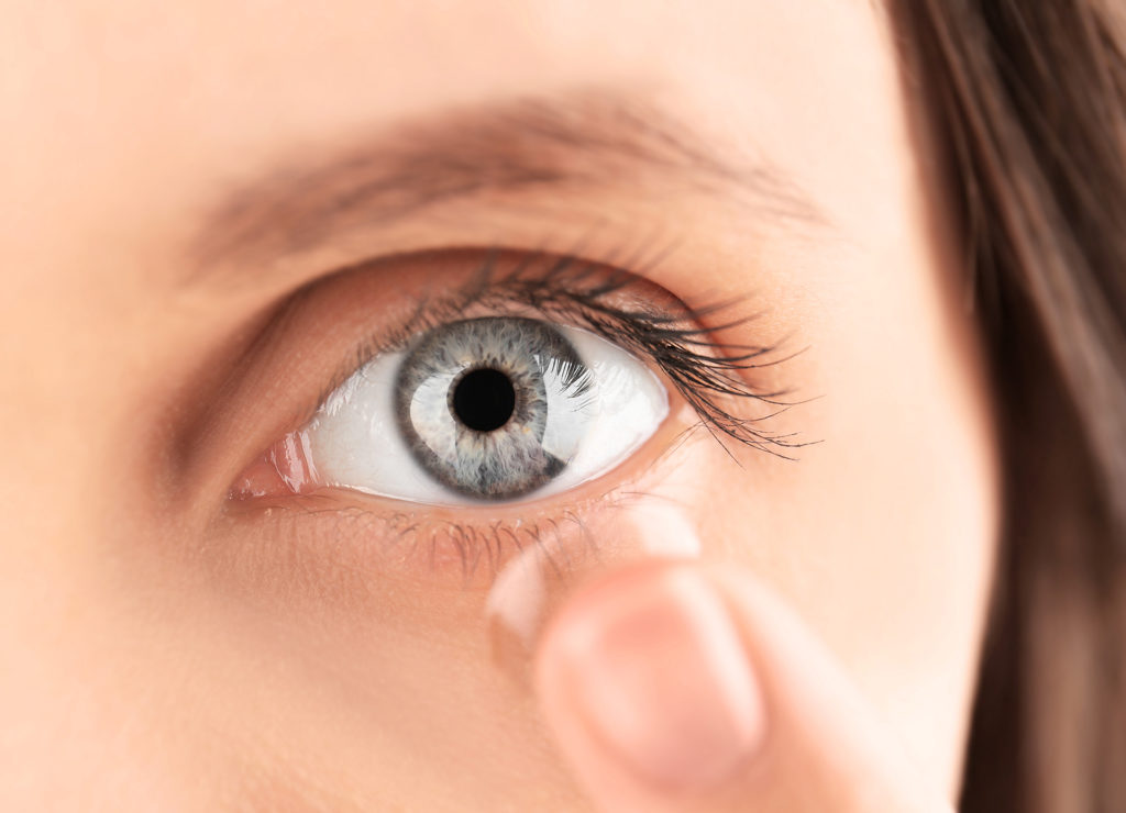 Close up view of young woman putting contact lens in her eye;