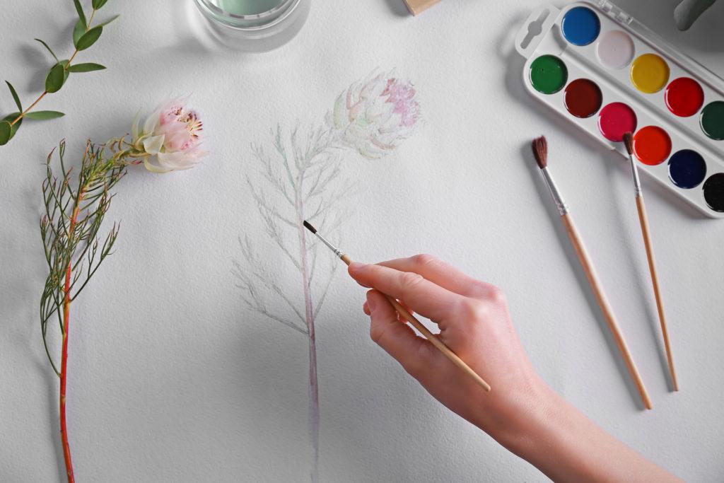 Woman drawing flower on album sheet;
