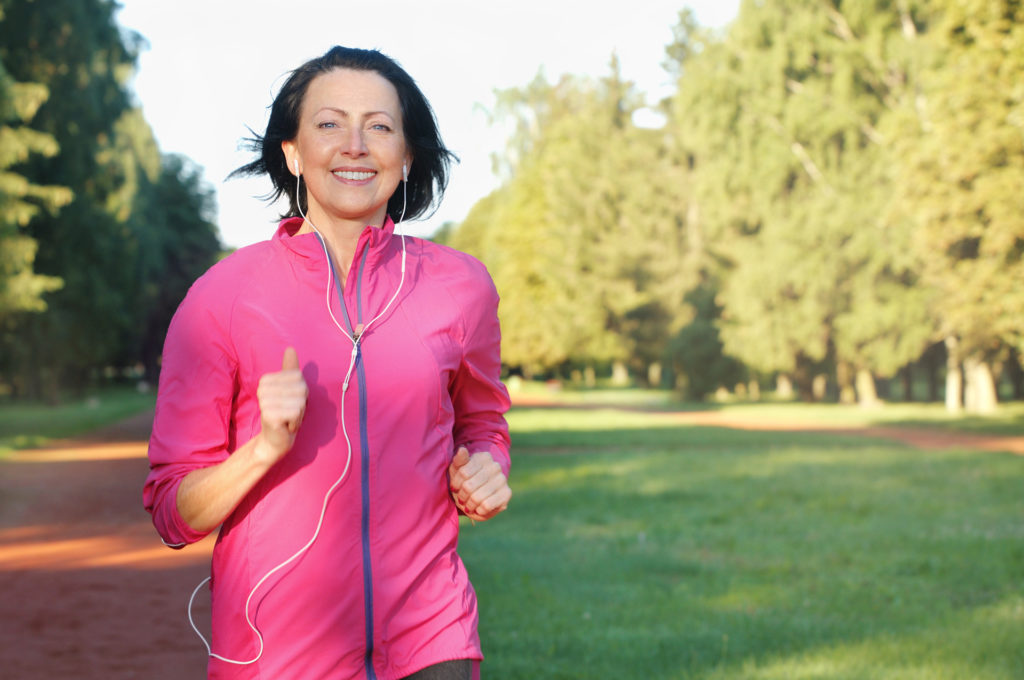 Portrait of elderly woman running with headphones in the park in early morning. Attractive looking mature woman keeping fit and healthy.;