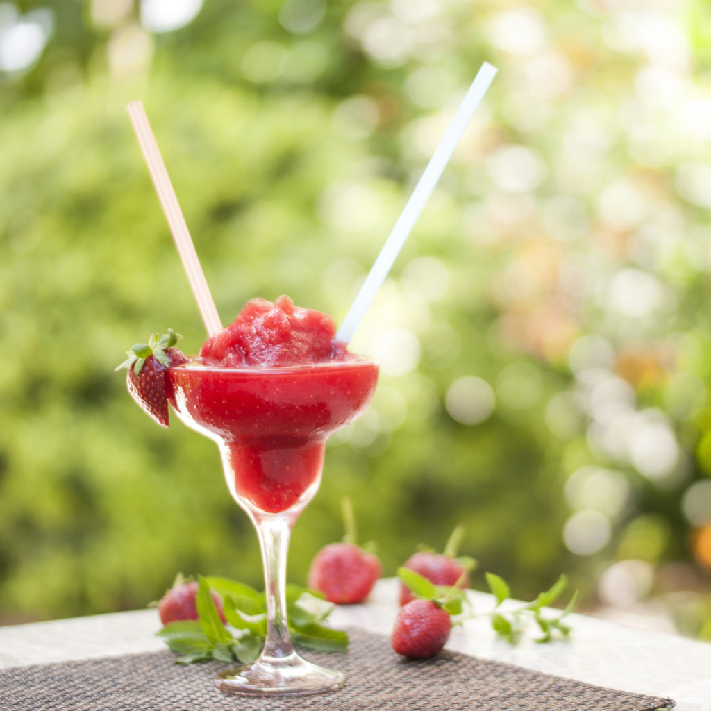 Cocktail glass of strawberry crushed ice and strawberries on a table in the garden