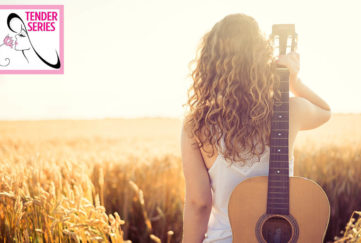Girl looks out over golden cornfield, guitar over her shoulder