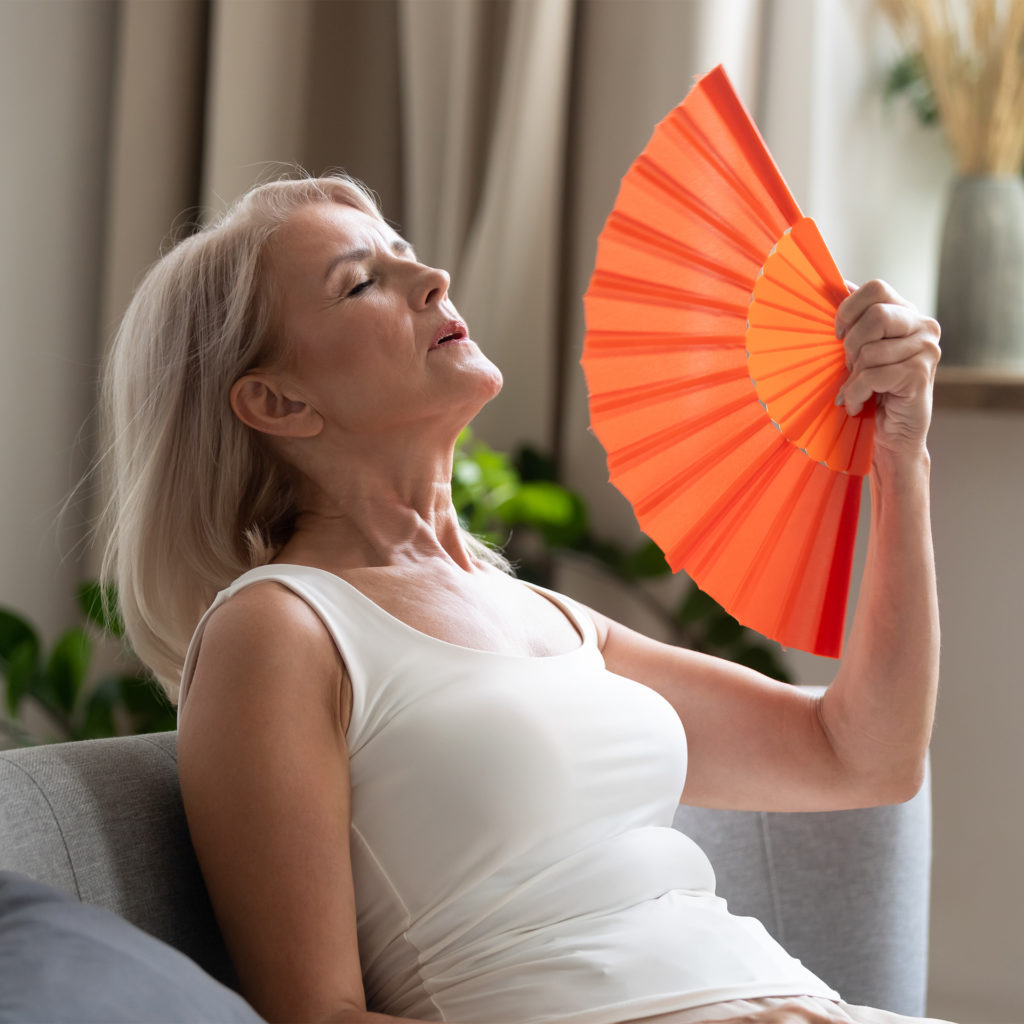 Mature woman leaning back on sofa fanning herself with an orange fan