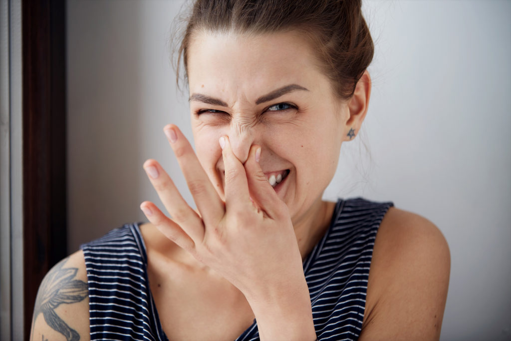 Female gesture smells bad. Headshot woman pinches nose with fingers hands looks with disgust something stinks bad smell situation. Human face expression body language reaction