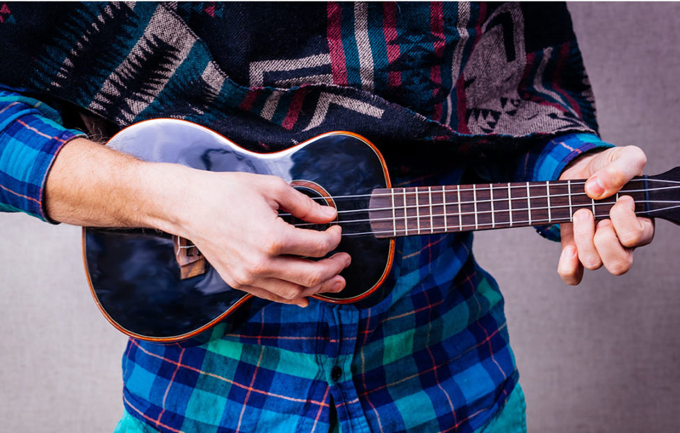 Person in bright checked shirt and ethnic scarf playing ukelele