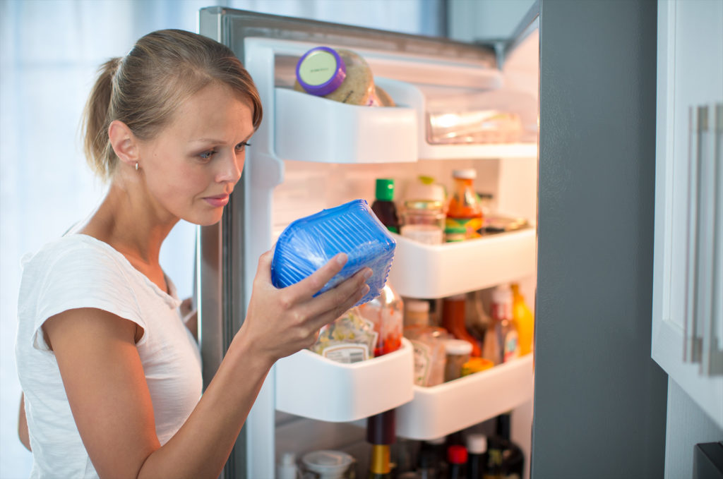 Is this still fine? Pretty, young woman in her kitchen by the fridge, looking at the expiry date of a product she took from her fridge