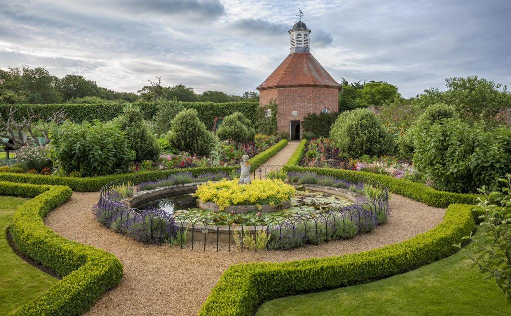 Beautiful circular path and box hedge around circular bed and old brick dovecote