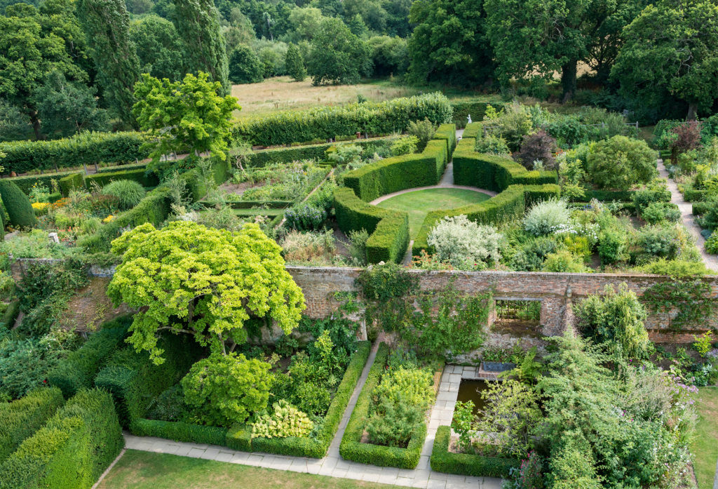 View from a window of beautiful garden with trees, beds and circular hedge with paths, parkland beyond