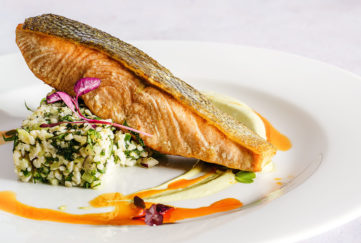"Fillet of trout on plate balanced on ""block"" of tabbouleh, grains and herbs, orange saffron sauce drizzled around"