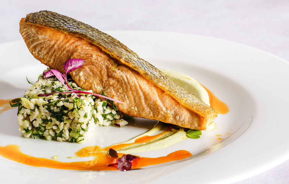 """Fillet of trout on plate balanced on """"block"""" of tabbouleh, grains and herbs, orange saffron sauce drizzled around"""