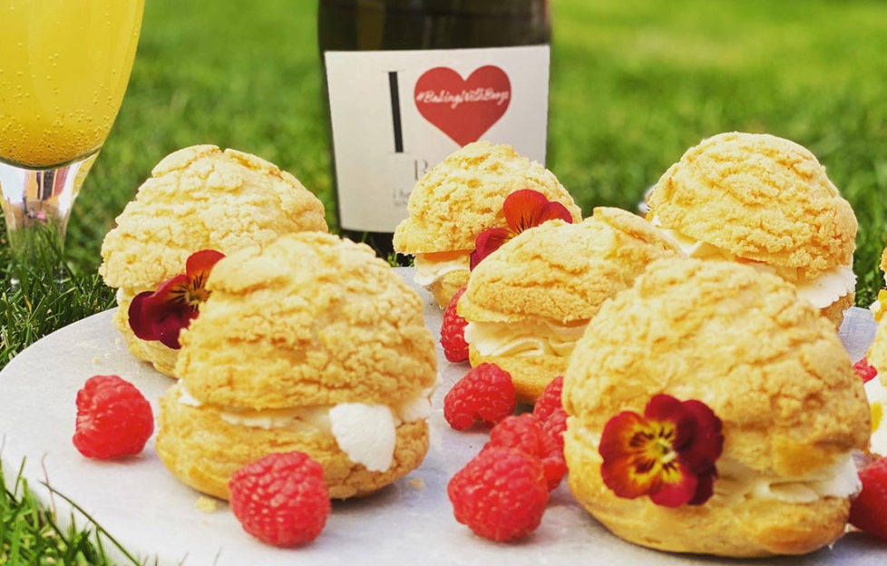 Plate of cream puffs on a plate outdoors with raspberries, flowers and I Heart Prosecco bottle