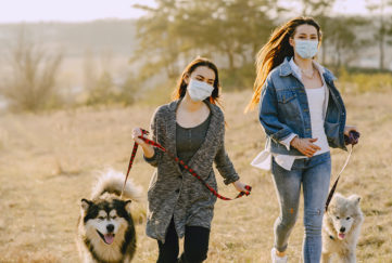 2 young women wearing face masks walking husky type dogs across a field