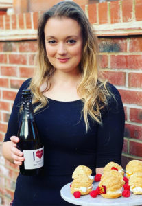 Smiling blonde girl by brick wall outdoors, holding plate of cream puffs and bottle of I Heart Prosecco