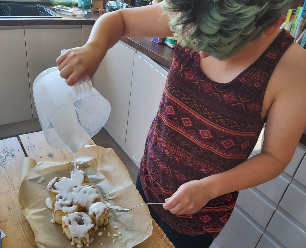 Young woman pouring icing from jug onto baked cinnamon bread