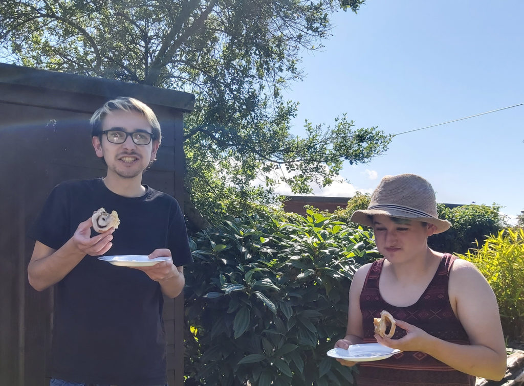 Young man and woman in a garden eating cinnamon roll bread