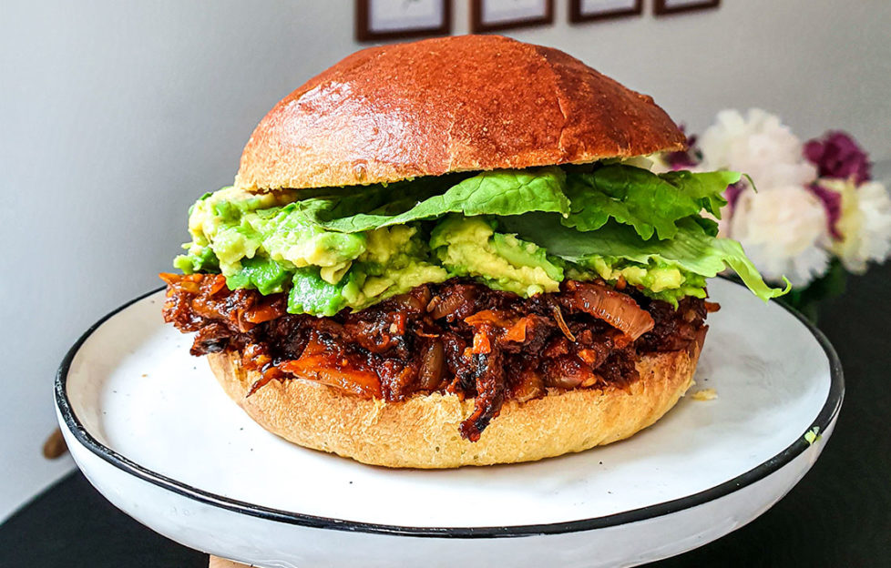 Large brioche roll filled with mashed avocado and savoury mushroom mixture