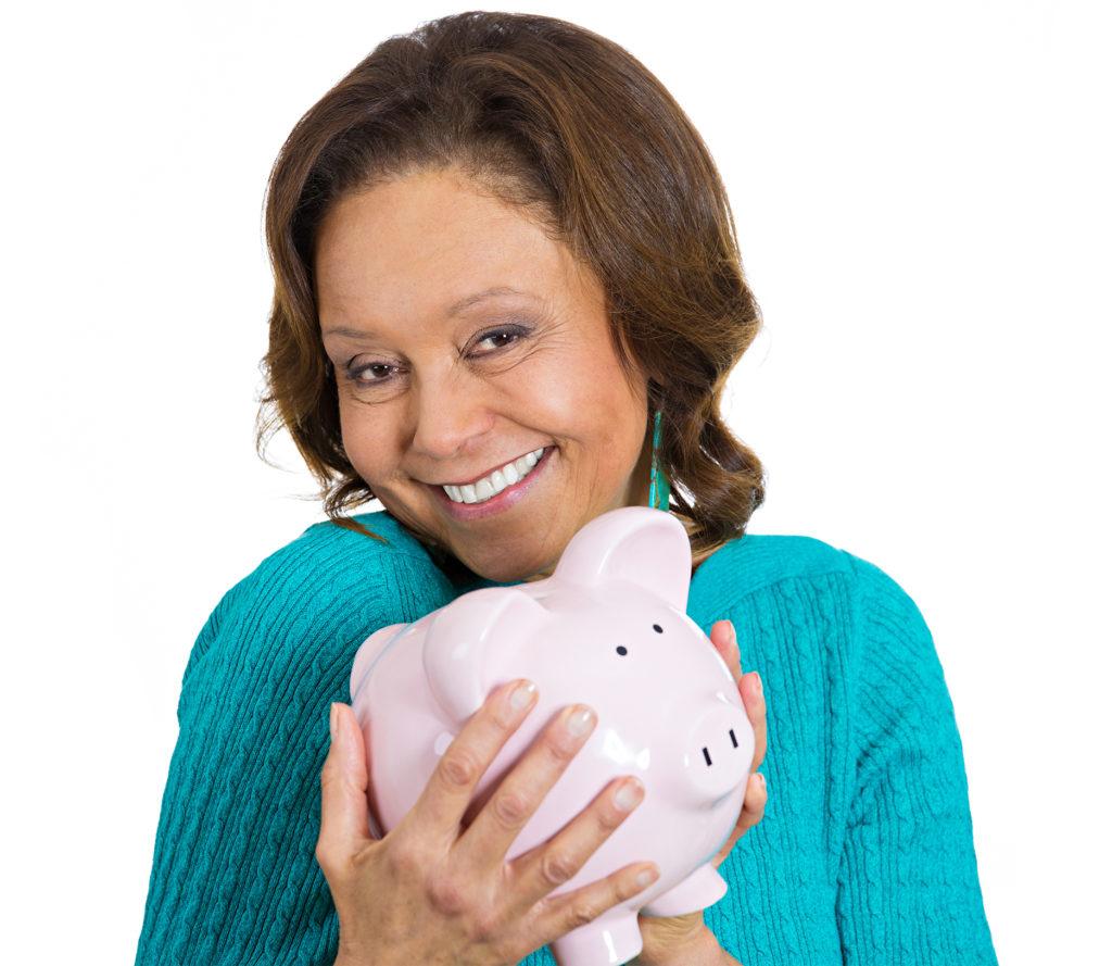 Mature woman cuddling piggy bank, smiling