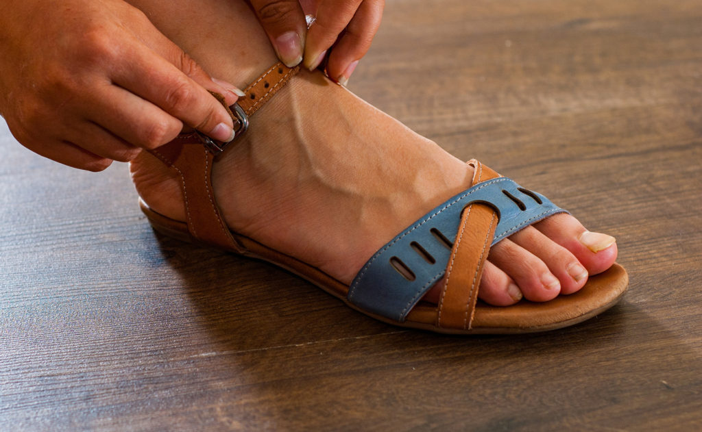 Woman fastens strap on leather sandals