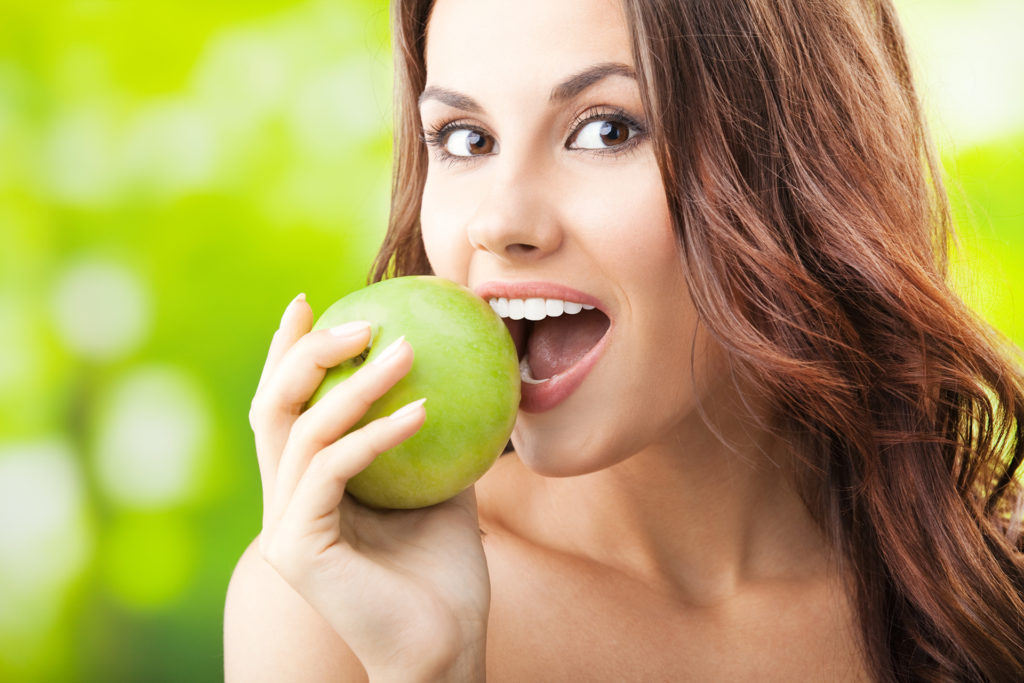 Young woman eating apple, outdoors;