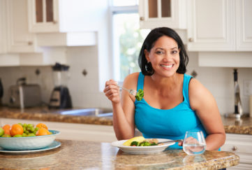Overweight Woman Eating Healthy Meal in Kitchen;