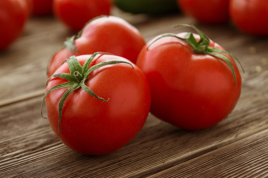 Close-up of fresh, ripe tomatoes on wood background;