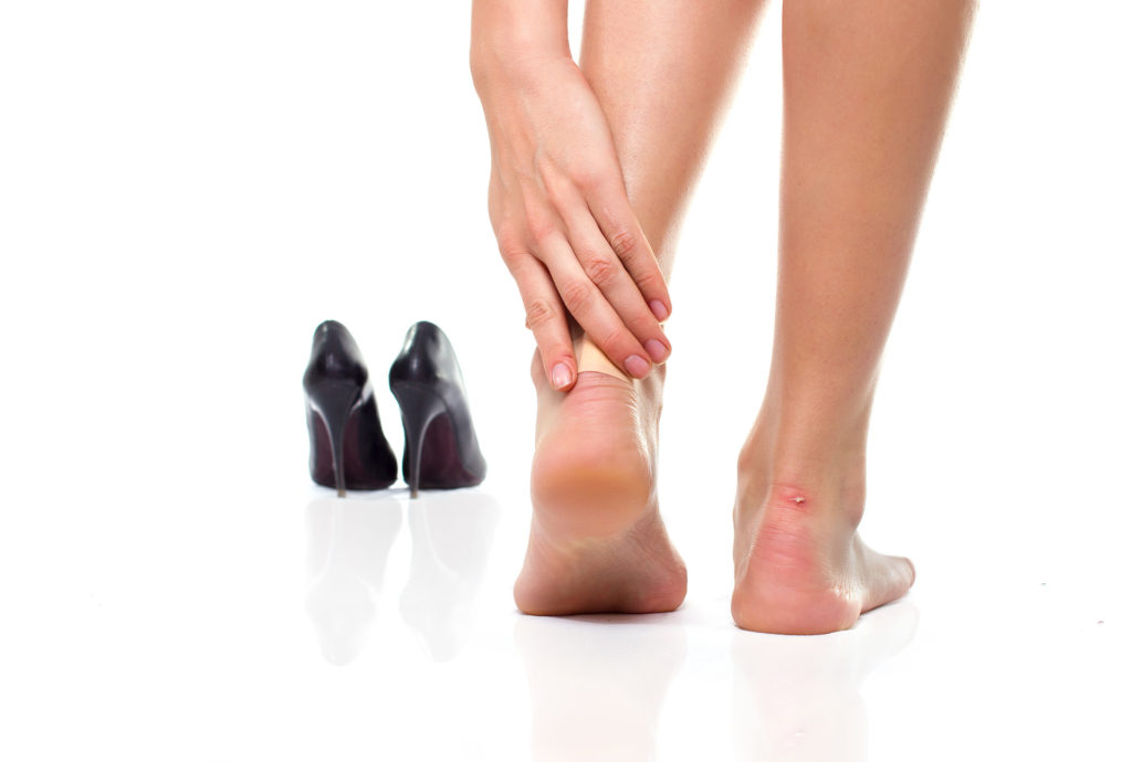 female feet in pain after wearing high heeled shoes;