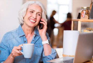 Older woman talking on mobile phone with cup of coffee