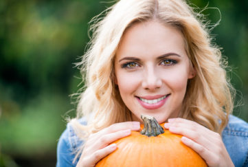 Close up, Beautiful young blond woman holding orange pumpkin;
