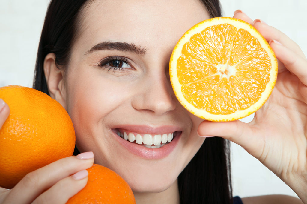 Woman holding up oranges cut in half to her face