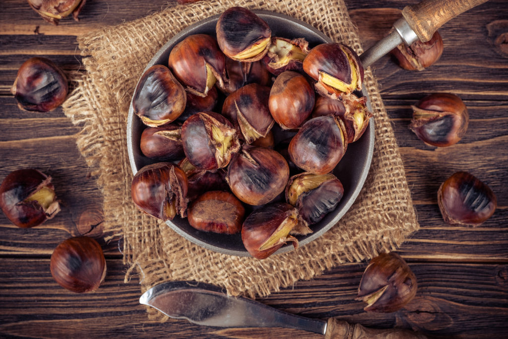 chestnuts in a pan on a wooden background;