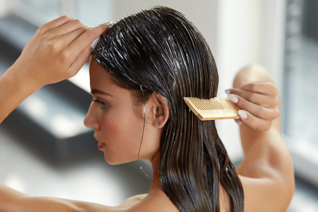 Hair Beauty. Closeup Of Beautiful Woman Hairbrushing With Comb And Using Conditioner. Young Female Model Putting Refreshing Mask On Long Wet Hair With Wooden Comb. Health Care.