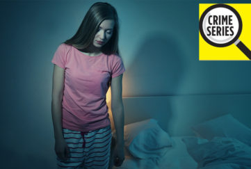 Young woman in pyjamas, eyes shut, gets out of bed in dark room