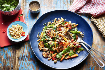 Blue plate with colourful mix of golden mushrooms, green coriander, cherry tomatoes, orange papaya and fried minced chicken