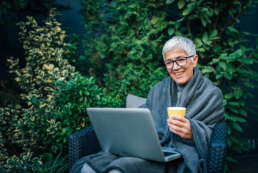 Mature woman in garden, wrapped in grey blanket, holding cup of tea, using laptop