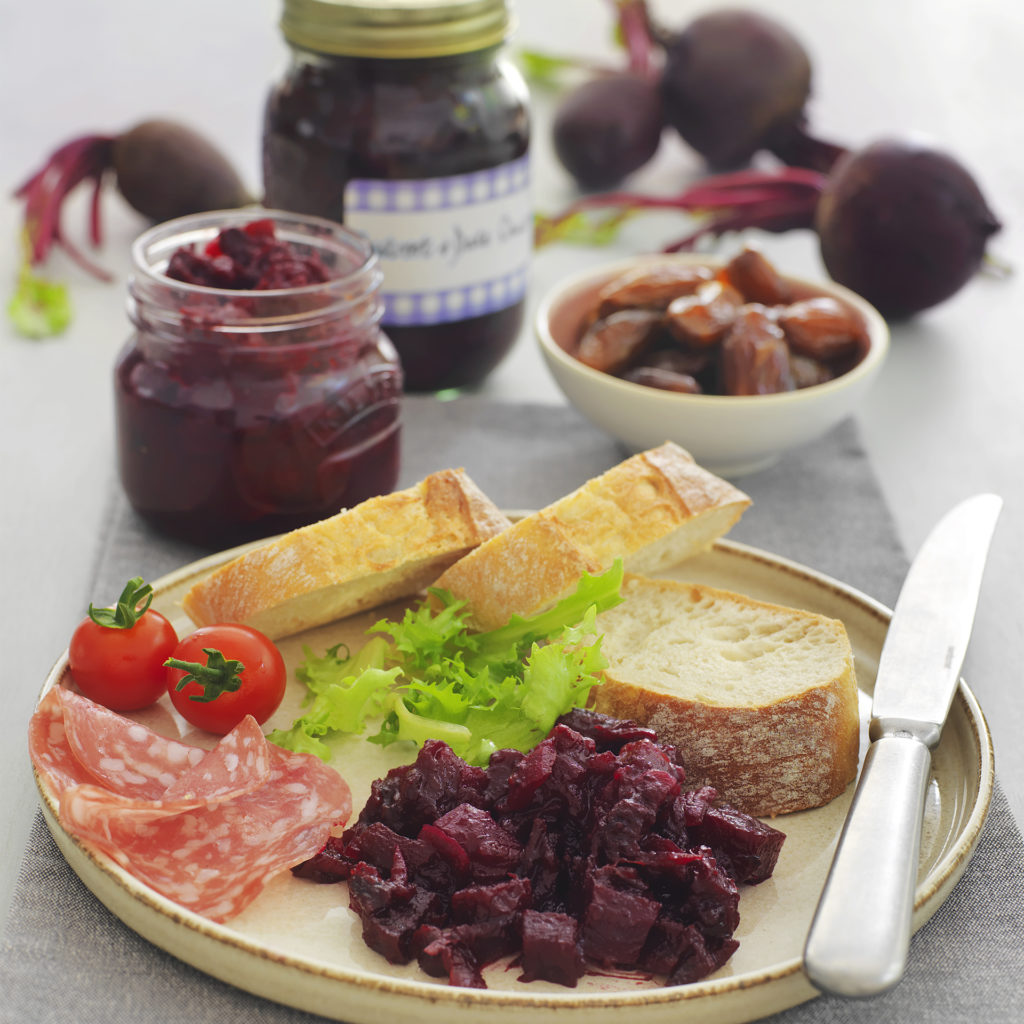 2 jars of homemade beetroot chutney, 2 fresh beetroot with leaves and a plate of bread, salami, salad and chutney