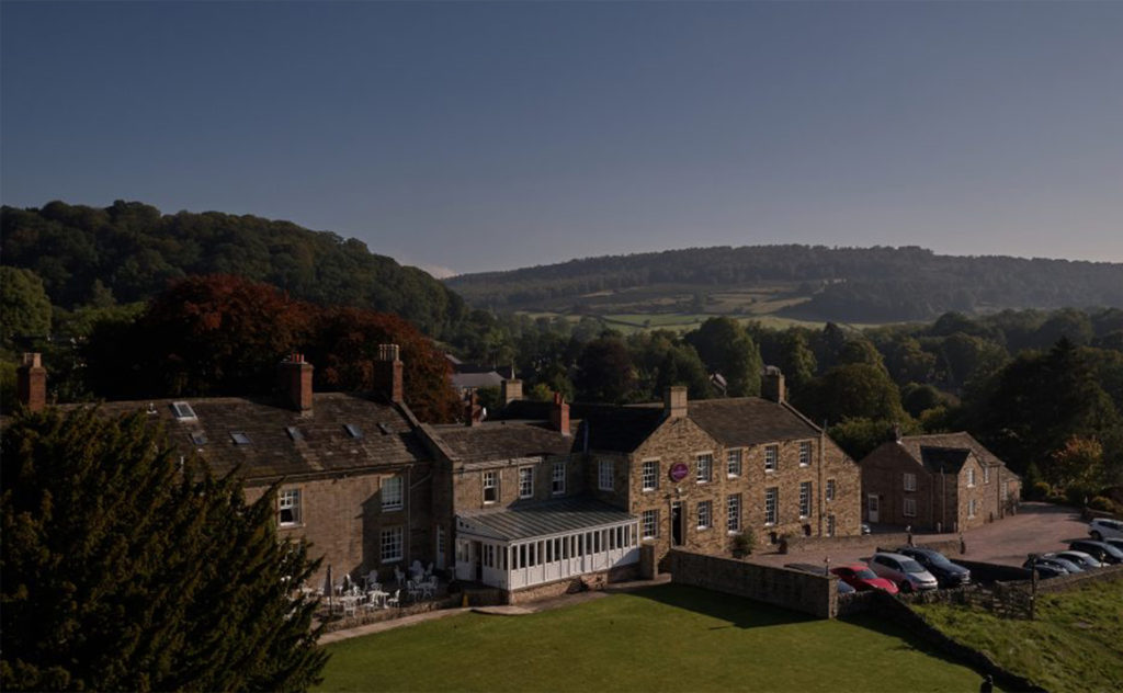Traditional stone built hotel set amid wooded hills