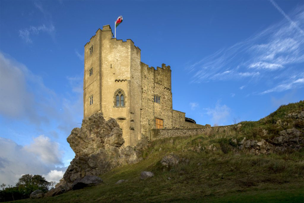 Medieval looking castle on rocky outcrop, blue sky, flag flying
